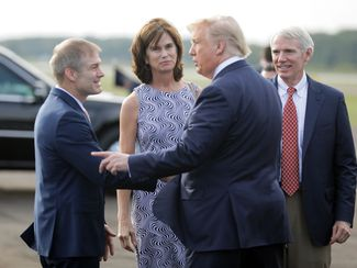 U.S. Sen. Rob Portman, back right, and his wife, Jane Portman, watch as President Donald Trump is greeted by U.S. Rep. Jim Jordan, left, after Trump arrives in Lima, Ohio, on Air Force One, Sept. 22, 2019. (Bill Lackey/Dayton Daily News via AP)